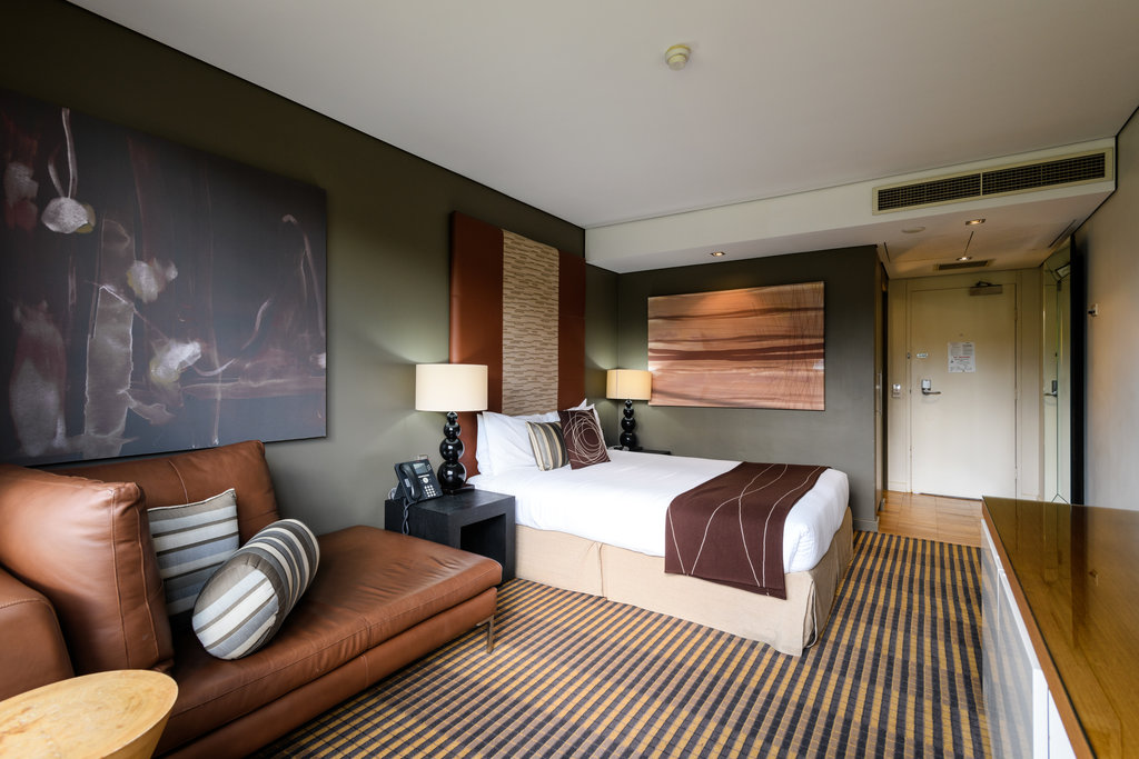 Interior room view of MGSM's north ryde executive hotel, picturing the bedroom with lamp, artwork, bed with brown and white pillows