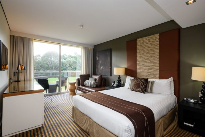 Interior room view of MGSM's north ryde executive hotel, picturing the bedroom with white and brown styling, including bed, lamps, couch and writing desk