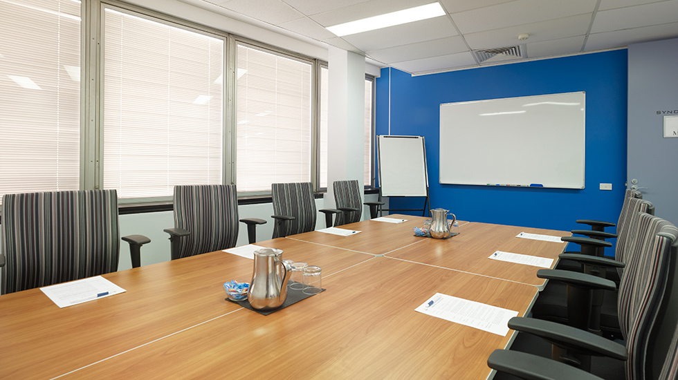 A small conference room with desks and chairs