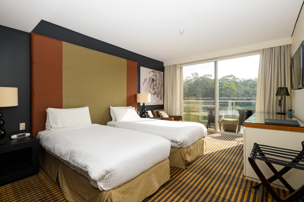 Interior room view of the MGSM north ryde executive hotel, picturing the living area with couches, tables, lamps and artworks. With the doorway open to the bedroom viewing the corner of the bed